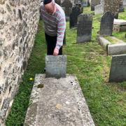 Rabbi Doug Kahn places a memorial stone at the grave of Solomon Teacher.